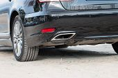 foto of exhaust pipes  - Chrome exhaust pipe of black powerful sport car bumper - JPG
