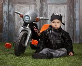 pic of tricycle  - Adorable toddler wearing a leather jacket and bandanna and sitting in the grass next to a toy tricycle - JPG