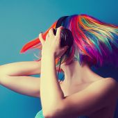 stock photo of wig  - beautiful woman wearing colorful wig and headphones against blue background
