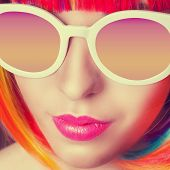 picture of wig  - beautiful woman wearing colorful wig and white sunglasses against wooden background - JPG