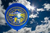 pic of nebraska  - balloon in colors of nebraska flag flying on blue sky - JPG