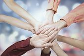 picture of joining hands  - Closeup of business people joining hands together shot against bokeh background - JPG