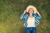 pic of beautiful senior woman  - Beautiful senior woman lying on a grass in a park - JPG