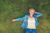 foto of beautiful senior woman  - Beautiful senior woman lying on a grass in a park - JPG