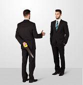 image of backstabbers  - Two opposing businessman shake hands - JPG