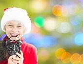 foto of santa claus hat  - little girl in Santa Claus hat holding alarm clock showing twelve o - JPG