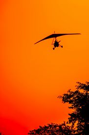 stock photo of ultralight  - The silhouette of a microlite aircraft on final approach as it gets ready for landing over the tree tops as the sun is setting in a red orange and yellow sky - JPG