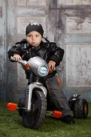 stock photo of skull crossbones  - Adorable toddler wearing a skull and crossbones scarf and leather jacket and riding a toy tricycle - JPG