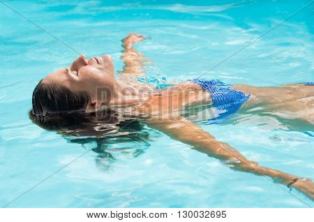 Young woman relaxing in swimming pool. Smiling woman with eyes closed lying on her back floating in