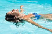 Young woman relaxing in swimming pool. Smiling woman with eyes closed lying on her back floating in  poster