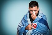 Portrait of a sick man with the flu, allergy, germs,cold, blowing his nose with tissue and holding a poster