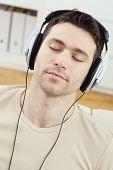 Постер, плакат: Случайный человек прослушивания музыки с наушниками на дому расслабляющий с закрытыми глазами улыбаясь
