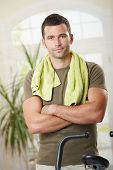 picture of personal trainer  - Personal trainer wearing sportswear and towel standing in living room at home with training bike - JPG