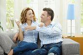 Постер, плакат: Молодая пара смотреть телевизор у себя дома сидя на диване держа в руке дистанционного управления
