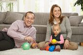 foto of nuclear family  - Happy smiling parents sitting with baby girl holding ball in hands at  home - JPG