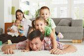 picture of nuclear family  - Happy family having fun posing for camera on floor of in living room at home - JPG