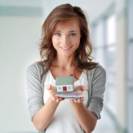foto of real-estate agent  - Beautiful young woman holding euros bills and house model over white  - JPG