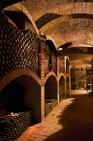 foto of wine cellar  - Winebottles stacked in the old cellar of the winery - JPG