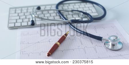 poster of Stethoscope On Cardiogram Concept For Heart Care On The Desk.blue Toned Images.