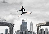 Business Woman Jumping Over Gap In Concrete Bridge As Symbol Of Overcoming Challenges. Dark Sky And  poster