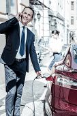 Absolutely Busy. Nice Handsome Busy Man Standing Near His Car And Refilling It While Having A Phone  poster