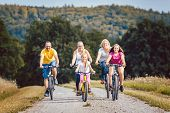 Family riding their bicycles on afternoon in the summer countryside poster