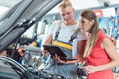 Reliable auto mechanic showing to a female customer the engine error codes scanned by a car diagnost poster