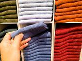 Women Hand Pick The Dark Blue Sock From Socks Stack On Shelves For Sale In Clothing Store poster