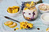 Breakfast In A Glass Jar: Homemade Granola, Banana, Fresh Berries, Yogurt On A Light Textile Backgro poster