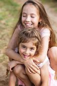 Two Beautiful Little Girls Embracing And Laughing At The Seaside. Happy Kids Outdoors poster