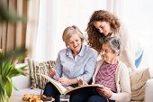 A Teenage Girl, Her Mother And Grandmother Looking At Old Photographs At Home. Family And Generation poster