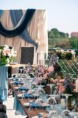 Vertical Image Of Wedding Catered Event Setting, Flowers, Candles, White Plates, Blue Napkins, Woode poster