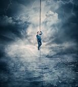 Businessman Salvation, Surviving The Storm Buiness Concept As A Scared Man Hanging On A Chain Above  poster