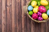 Easter background with colorful Easter eggs in basket on wooden background poster