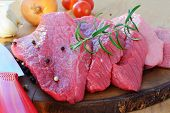 Sliced Red Meat On Wooden Board With Herbs And Spices. Veal Beef Slices Ready For Schnitzel Or Barbe poster