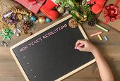 Kid Writing New Year Resolution On Black Board With Decorations And Gift Boxes, New Year And Merry C poster