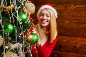 Cute Girl Is Decorating The Christmas Tree Indoors. Christmas Decorations. Fashion Portrait Of Model poster