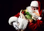 Jolly Santa Claus Is Holding A Big Sack Full Of Fruits And Vegetables. Enjoy A Healthy Christmas Din poster