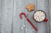 Red Mag Of Drink With Candy Cane And Christmas Gigerbread On Wooden Background. Top View. poster