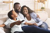 Happy Black Family Of Three Watching Tv, Relaxing Together At Home, Enjoying Weekend Together. poster