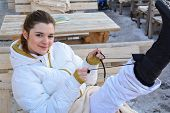 Beautiful, Cheerful And Satisfied Girl In White Ski Suit  Putting On Snow Boots After Active Ski Day poster