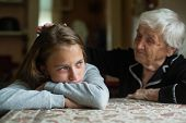 A crying teenage girl is strokes head by an old grandmother. poster