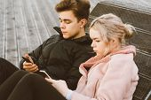 Loving Teenagers On Date Look At Mobile Phones, Sit On Park Bench In Fall. Immersion In Virtual Worl poster