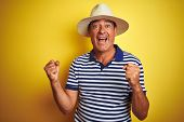 Handsome middle age man wearing striped polo and hat over isolated yellow background very happy and  poster