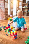 Young caucasian kid playing at kindergarten with toys blocks. Preschooler boy happy at playroom buil poster