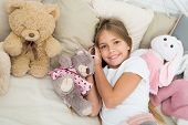 Comfortable Bedroom. Relaxing Before Sleep. Girl Enjoy Evening Time With Toys. Kid Lay Bed With Toys poster