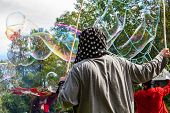 Iridescent Bubbles Are Seen Coming From A Structure Crafted With Bamboo And String, Held By A Pagan  poster