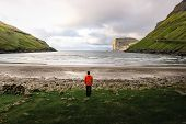 Tourist Standing At The Beach In Tjornuvik Located On The Coast Of A Beautiful Bay In The Faroe Isla poster
