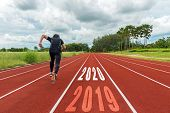 The Start Into The New Year 2020. Start Up Of Runner Man Running On Race Track Go To Goal Of Success poster