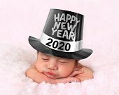 Newborn baby girl wearing a Happy New Year 2020 hat.  poster